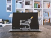Miniature shopping cart and laptop on a desk