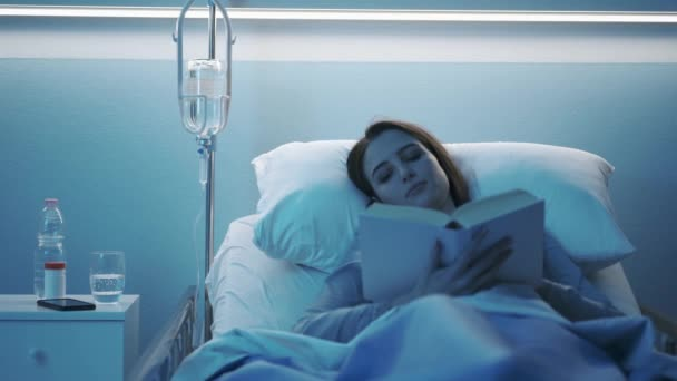 Patientin liegt im Krankenhausbett und liest ein Buch
