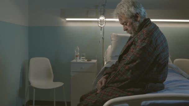 Sleepless senior man sitting on a hospital bed