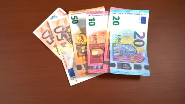Hand mit blauen Handschuhen und einer Gesichtsmaske mit dem Wort Coronavirus über einem Euro-Schein