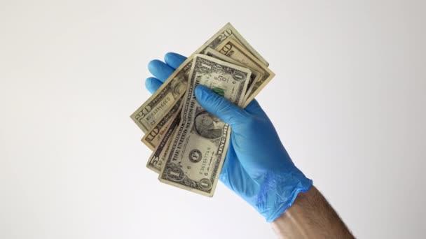 Hand mit Dollarscheinen und eine Gesichtsmaske mit dem Wort Coronavirus isoliert auf weiß