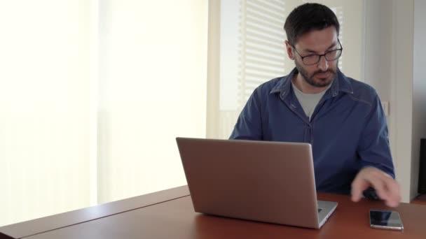 Mann arbeitet von zu Hause aus und greift zum Telefon