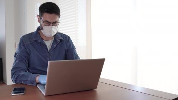 Mann mit Mundschutz und blauen Handschuhen greift zum Telefon