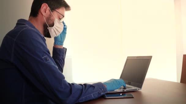 Mann mit Gesichtsmaske und blauen Handschuhen arbeitet von zu Hause aus und sorgt sich um Covid-19 Coronavirus