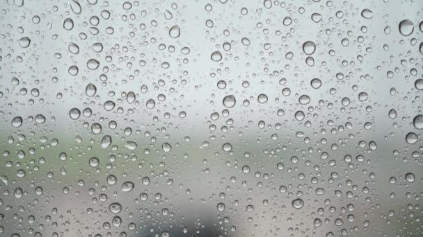 Dešťové kapky na povrchu okenních skel s kalným pozadím