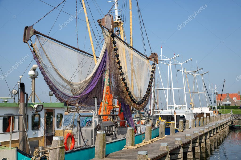 Harbor dutch fishing village Makkum with shrimp trawler drying nets