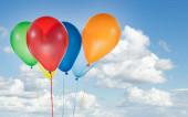 Barevné balónky k narozeninám a oslavy izolované na modré obloze
