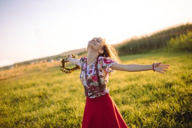 Girl enjoying nature on the field . The girl is joyful spinning with a wreath of flowers in her hands
