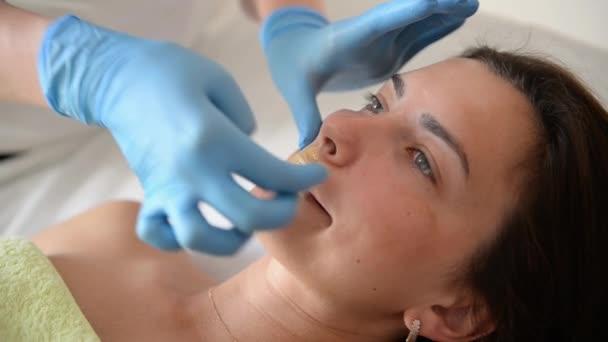Αφαίρεση το μουστάκι του μια γυναίκα με καυτό κερί στο σαλόνι ομορφιάς.  Σαλόνι ομορφιάς f0e65bdf0b2