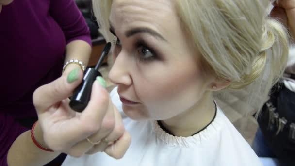 Vizážista dělá make-up řasy v mladou ženu. Make-upu. Kosmetické. Základ pro Make-up perfektní Make-up.Applying