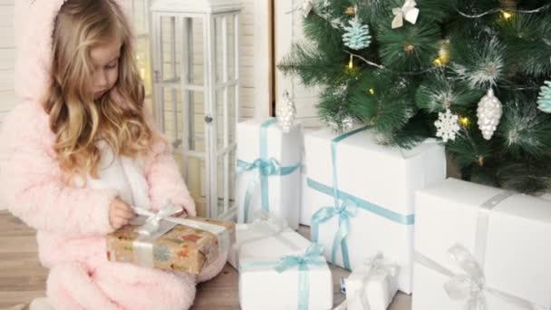 Frohe Weihnachten, kleines Mädchen öffnen eingewickelte Xmas ...