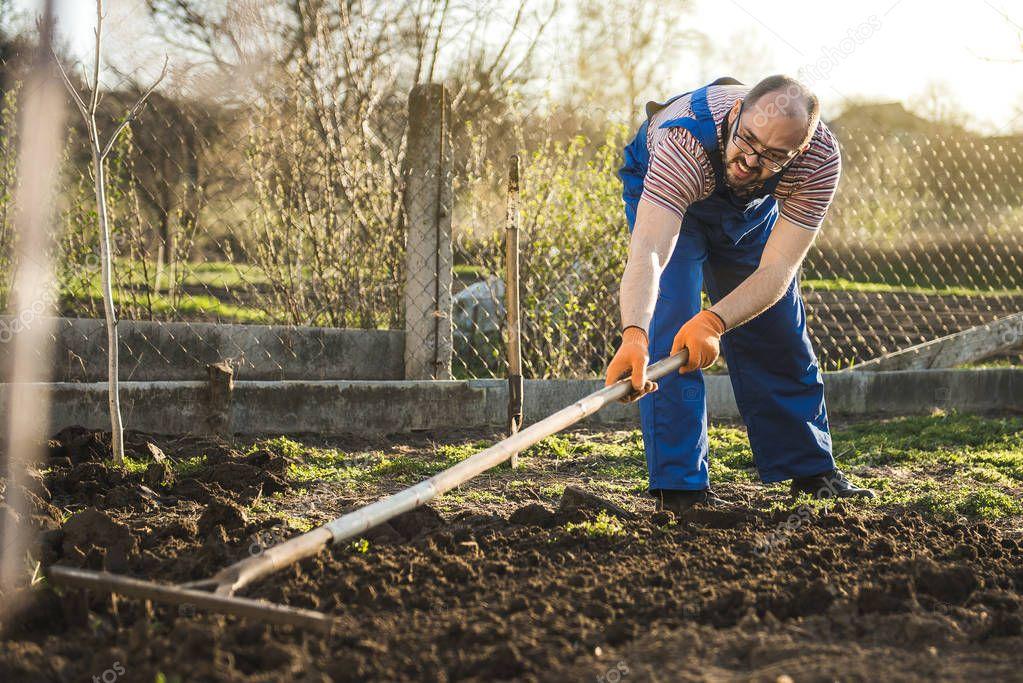Coltivatore che lavora nel giardino con l 39 aiuto di un for Livellare terreno