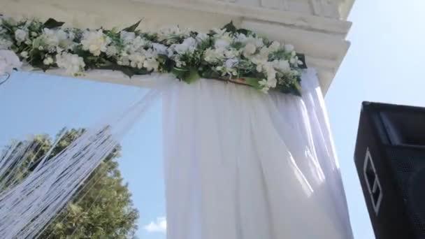Svatební oblouk, zdobené květy a velké vítr tkaniny. Střelba v pohybu. Svatební dekorace