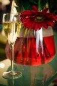 ein Glas Champagner neben einer Glasvase mit Blumen