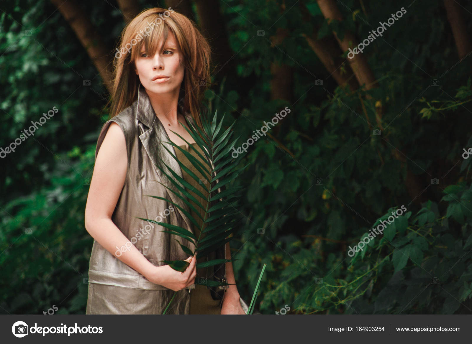 The girl looks away and waves a branch — Stock Photo