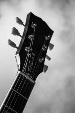 Black and white guitar with smoke in the background