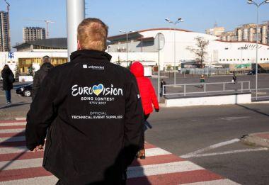 KYIV, UKRAINE - APRIL 21, 2017: Worker of Eurovision song contest walks near International Exhibition Centre in Kyiv, Ukraine stock vector