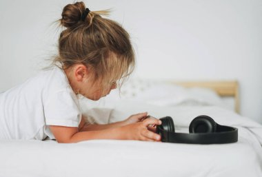 Cute toddler girl with fair hair with headphones with mobile on the bed in bright interior