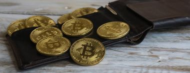 Golden Bitcoins with leather wallet on a wooden table .Close up side view