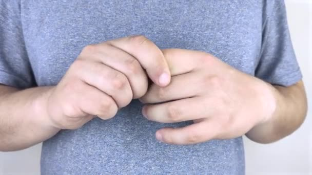 Bolest v kloubech prstů. Muž si mnul prsty, které ho bolely a škubaly. Artritida kloubů a jejich léčba.