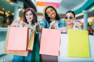 Beautiful stylish young women showing shopping bags and smiling, young girls shopping concept stock vector