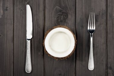 coconut half with metal fork and knife