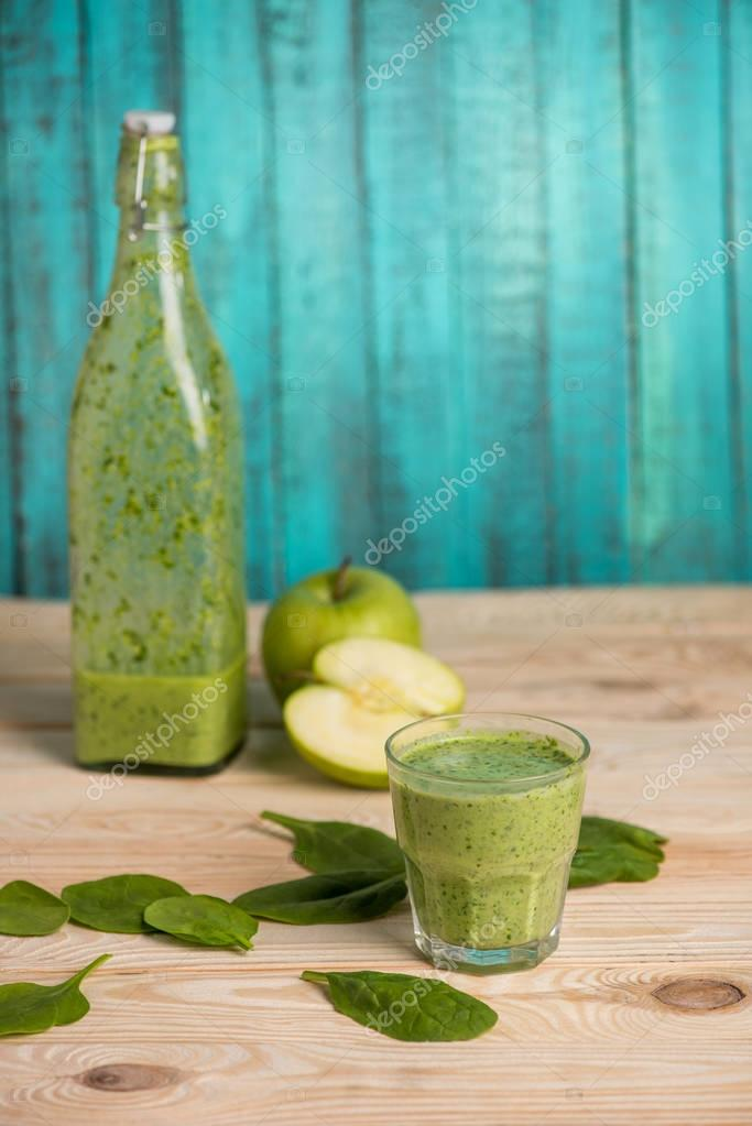 apples with smoothie in glass on wooden table