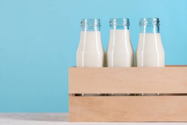 Glass bottles with milk in wooden box on tabletop at blue background stock vector