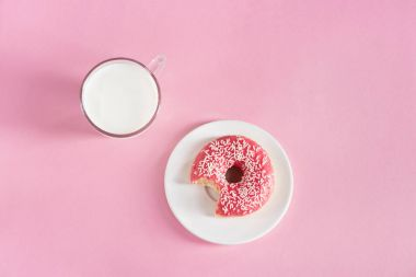 glass cup of milk with donut on plate
