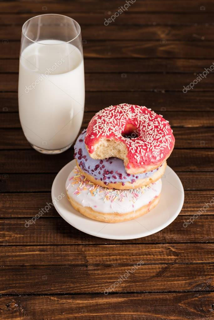 glass of milk with donuts on plate