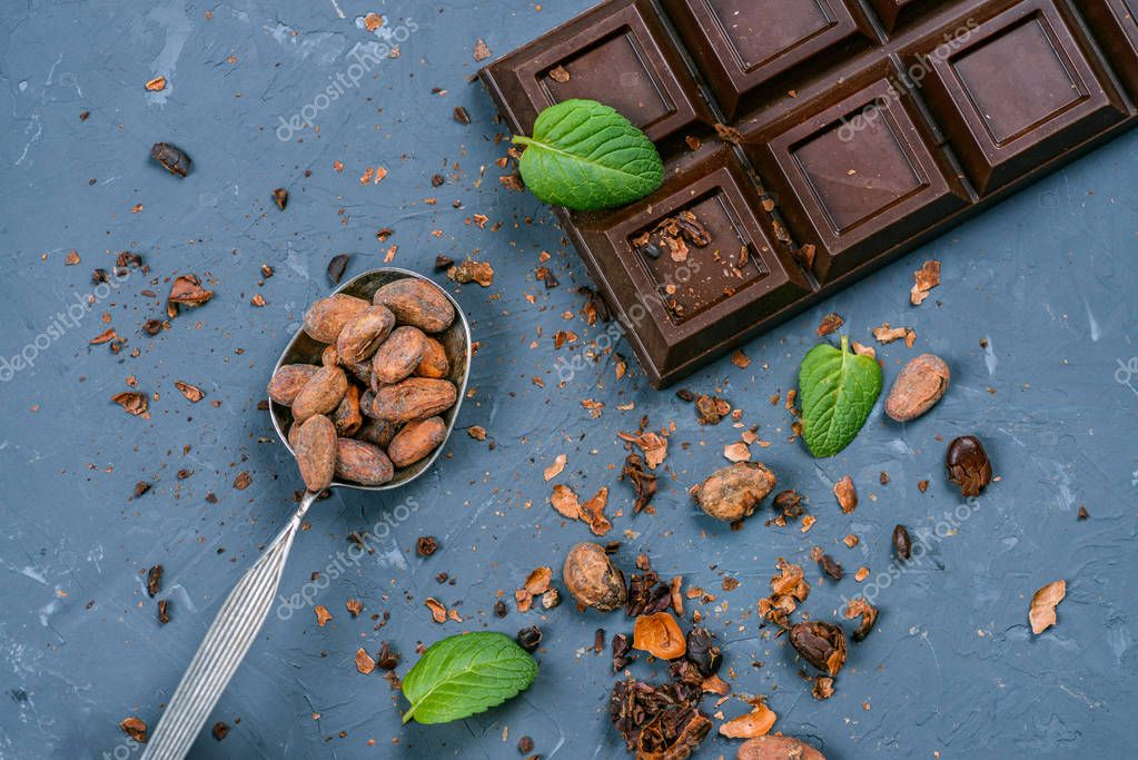 chocolate bar and spoon with cocoa beans