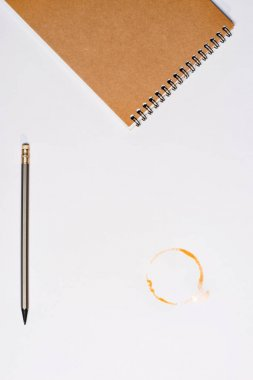 notebook with pencil and coffee stain