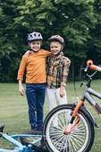 Fotografie děti v přilbách stojící vedle kola v parku