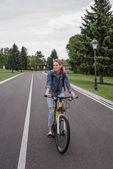 Fotografie žena jedoucí na kole na asfaltové silnici