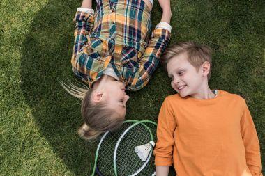 kids lying on green lawn
