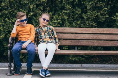 adorable kids sitting on bench at park
