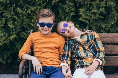 Smiling children sitting on bench at park