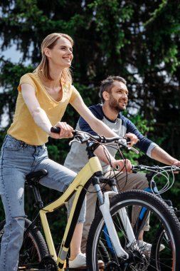 smiling couple riding bicycles at park