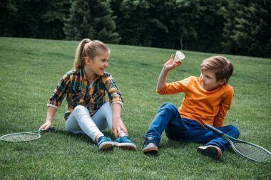 adorable kids sitting on grass at park