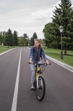 Woman riding bicycle on asphalt road
