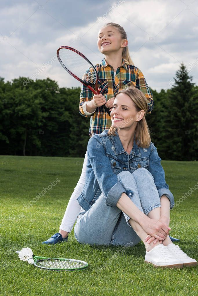 mother and daughter resting on green lawn
