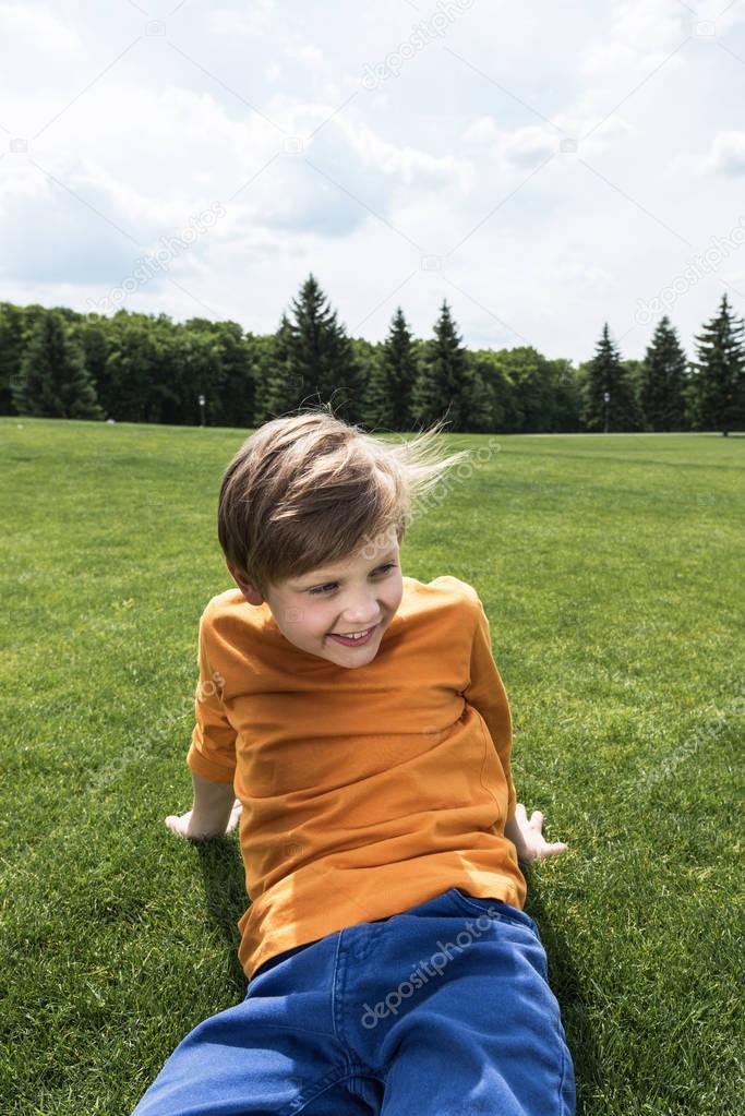 boy resting on green lawn