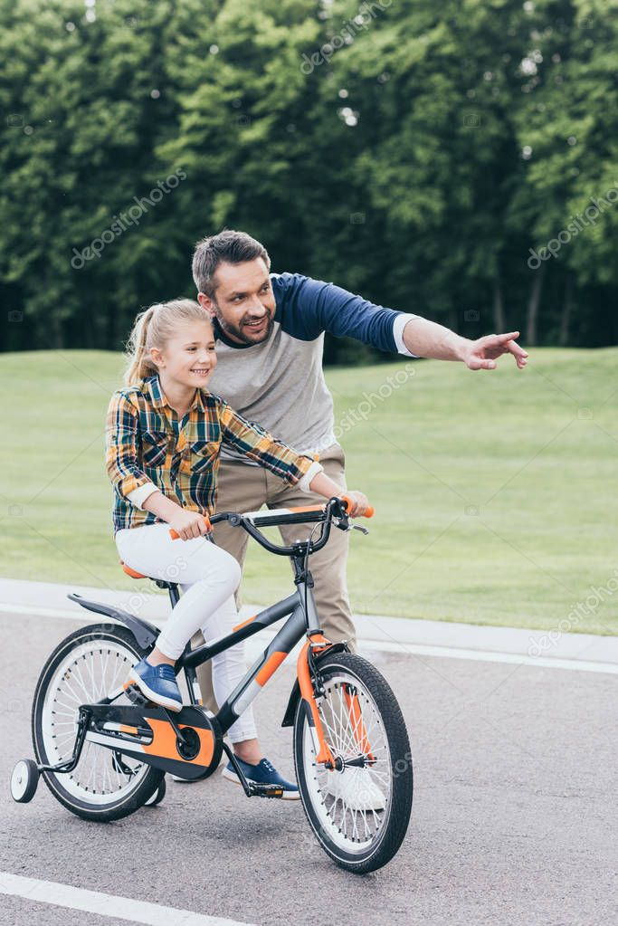 father teaching girl riding bicycle