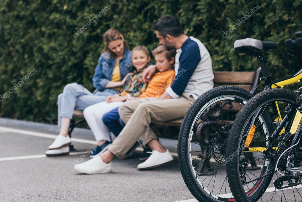 family sitting on bench at park