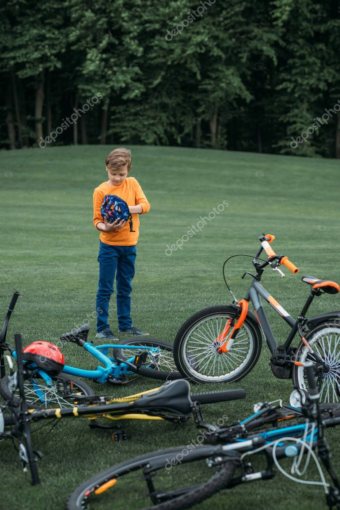 kid boy standing near bicycles at park
