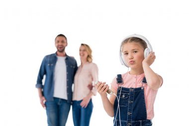 Little girl holding smartphone and listening music with headphones, parents standing behind, isolated on white stock vector