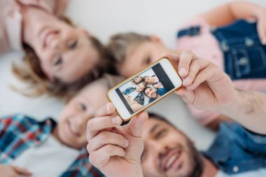 happy family taking selfie on smartphone