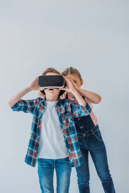 Casual kids using virtual reality headset together stock vector