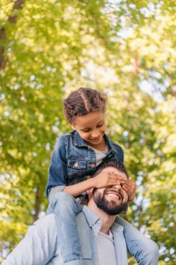 Father carrying daughter on shoulders