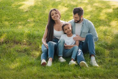 family resting on green lawn